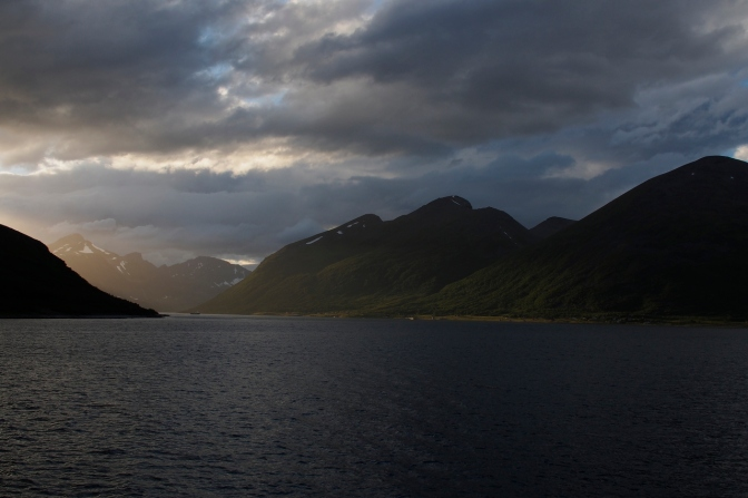 Sun illuminates a fiord near midnight along the northern Norwegian coast.