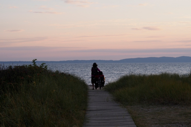 Jan walking her bike down to the beach at sunset but we could not camp there.