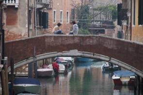 Sitting on a bridge in Venice.