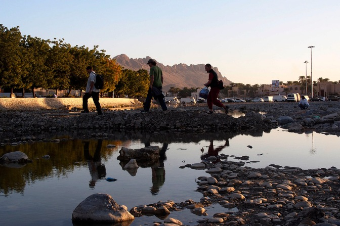 Crossing the wadi in Nizwa in search of a laundry.