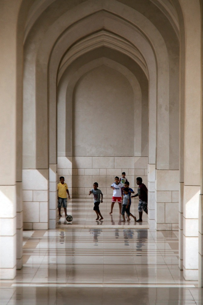 Kids playing football in one of the walkways at the Royal Palace in Muscat.