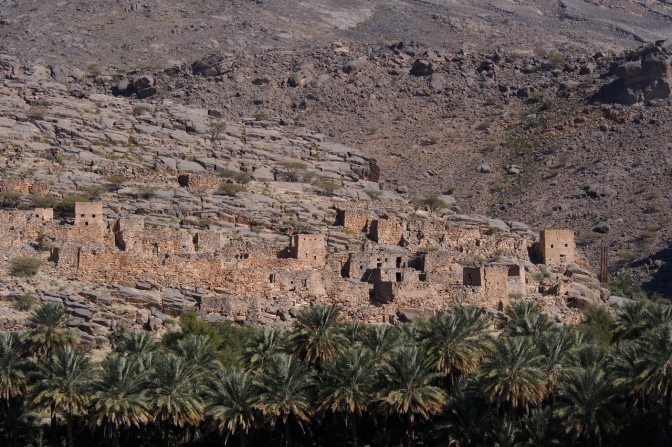 Abandoned mud-brick houses and oasis on the lower slopes of Jabal Shams.