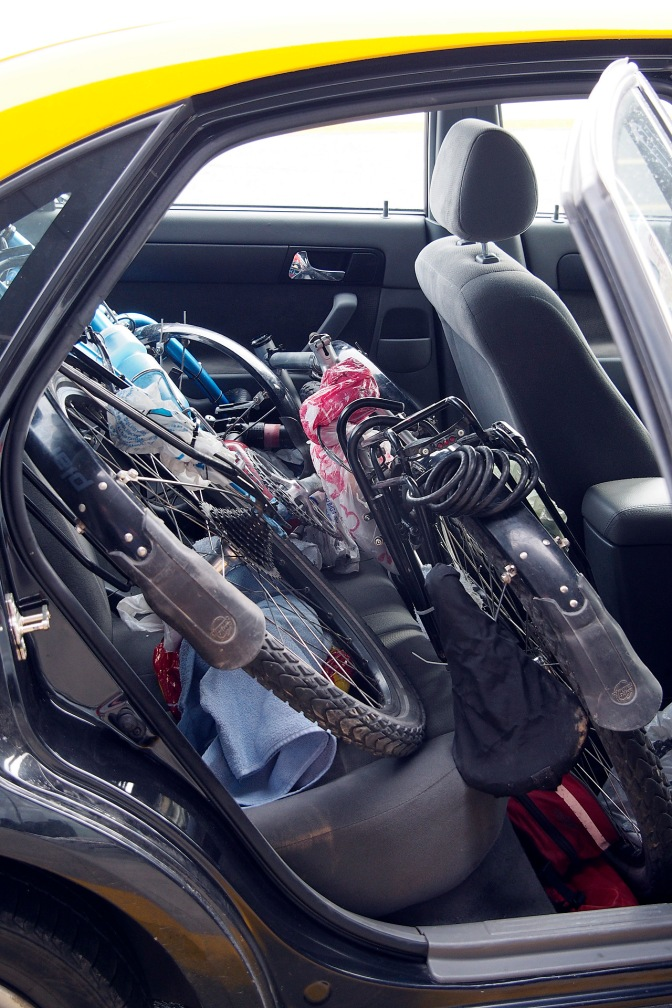 The bikes and all their bits in the backseat of the taxi.