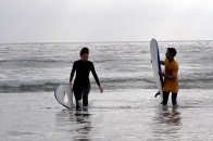 Surfers brave the cool waters at La Serena beach.