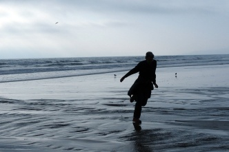 Paul crossing a stream on the beach.