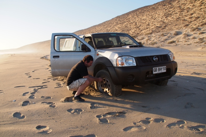 Andres letting some air out of the tires to get us out of the soft sand.