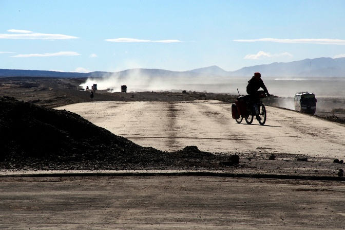 Cycling the not-yet-finished road to Uyuni while the trucks wreak a dusty havoc on the adjacent track.
