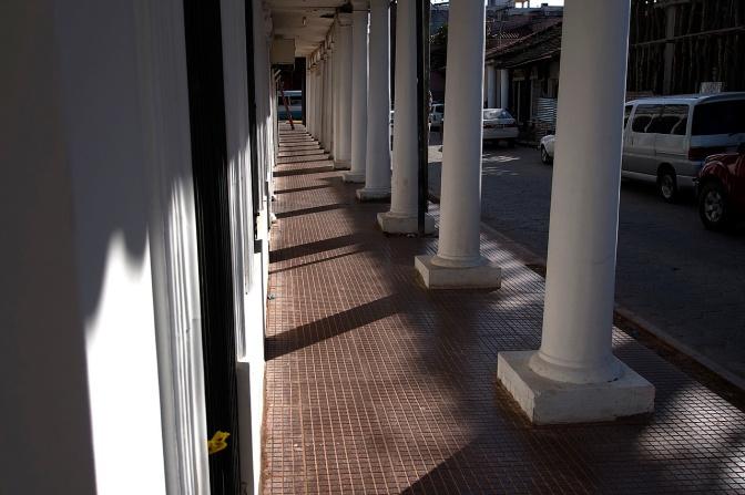 Light and shadow in an arcade along Avenida 24 de Septembre.