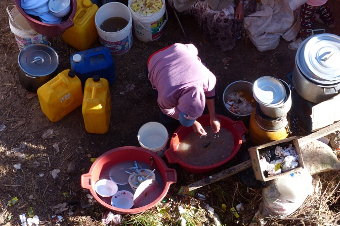 Washing dishes in not so clean water behind a beach-front food stall.