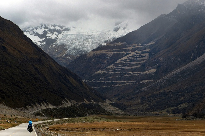 The view from below: Paul riding towards the ladder of switchbacks up to Punta Olimpica Pass in the Cordillera Blanca.