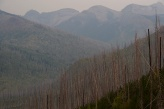 Smoke hangs in a valley where a forest fire raged years ago along the Going to the Sun Road.