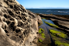 The sandstone shoreline is slowly changing shape as a result of the erosive forces of wind and water.